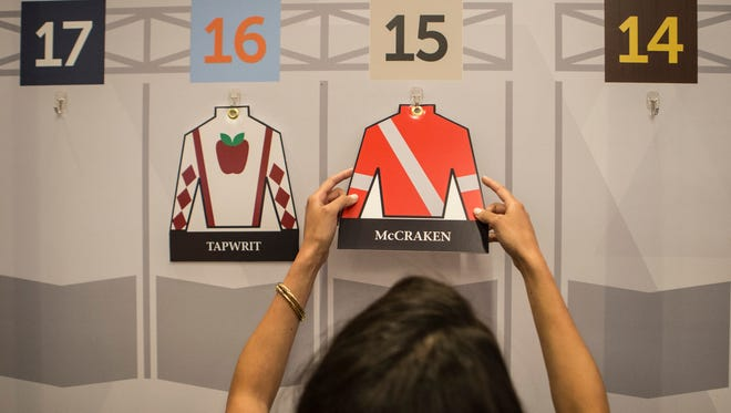Model Ariel Hawkins puts cutout jockey silks into their draw positions during the Kentucky Derby Draw event Wednesday morning at Churchill Downs. May 3, 2017