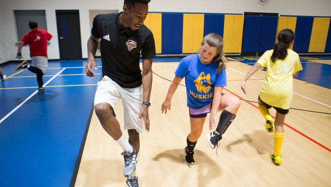 Louisville City FC soccer player Mark-Anthony Kaye, left, works with The de Paul School's Madison Mizell, 14, on her footwork during a visit by players to the school's soccer players. May 11, 2017