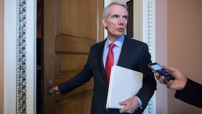 Sen. Rob Portman pauses for a reporter's question as he arrives at a closed-door GOP strategy session on the Republican health care overhaul on June 20, 2017.
