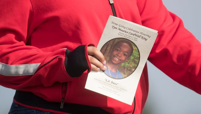 FILE - In this Sept. 24, 2016 file photo, a funeral service card bearing the likeness of Tyre King, the 13-year-old Ohio boy who was fatally shot by Columbus police, is carried by a mourner in Columbus, Ohio.  Columbus, Ohio, police officer Bryan Mason shot  King, after a suspected robbery last year feared a gunfight with the teen, who the officer said pulled a gun from his pants, records show.  Mason fired when he saw a laser sight on the gun, which turned out to be a BB gun, Mason said in a formal statement and interview with detectives obtained by The Associated Press through a records request.  (AP Photo/John Minchillo, File)