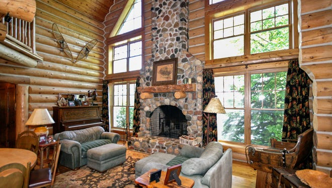 A massive stone fireplace stands in a wall of windows at 8777 North Shore Drive, Spicer.