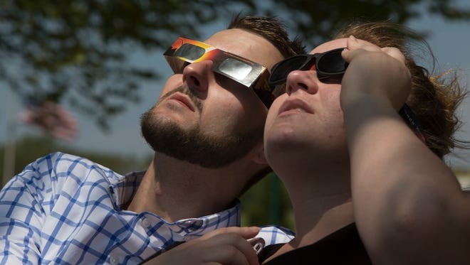 Matthew Dickey and Rachel Heatherly watched the solar eclipse of the sun from a park in Clarsville, Ind, across the Ohio River from Louisville. Aug. 21, 2017.
