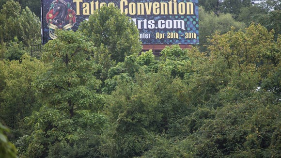 New state regulations allow cutting trees that block billboards such as this one on I-64 in Louisville. Aug. 22, 2017