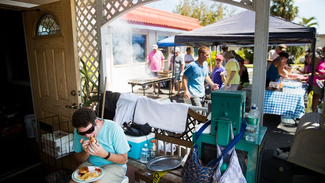 David Wheeler, a Marco Island resident, sits down to eat his food at Kretch's on Tuesday, September 12, 2017, two days after Hurricane Irma. Kretch's and CJ's teamed up to fire up the grills to feed hot meals for free to those without power.