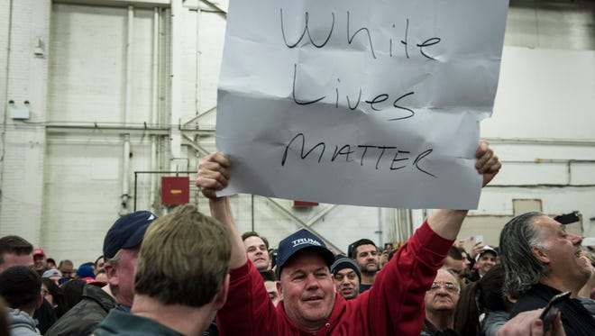"BETHPAGE, NEW YORK - APRIL 06: A Trump supporter holds up a ""White Lives Matter"" sign during a rally for Republican Presidential Candidate Donald Trump on April 6, 2016 in Bethpage, New York. The rally comes ahead of the April 15 New York primary. (Photo by Andrew Renneisen/Getty Images)"