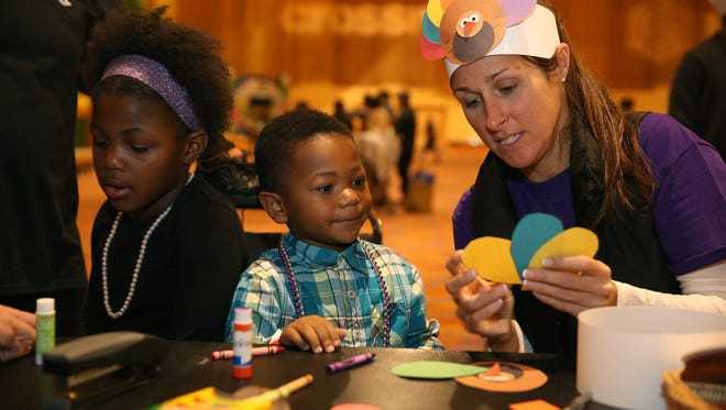 Kanilah Levy, left, and her brother Jordan Levy, 3, of Delhi Township get help with making a turkey from Megan Ball during Give Back Cincinnati's Fall Feast at Duke Energy Convention Center.