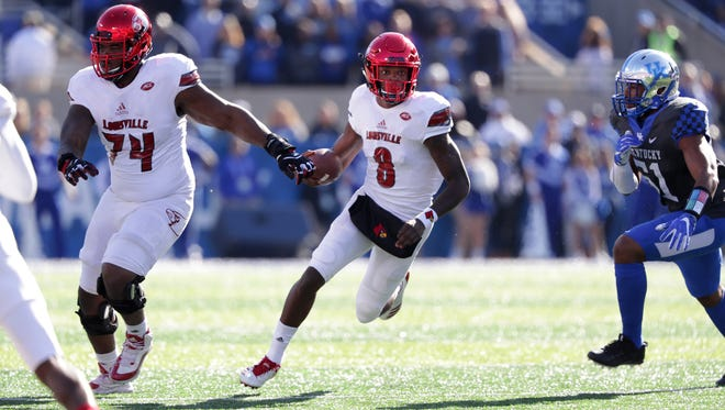 Louisville quarterback Lamar Jackson looks for running room during first quarter action against UK. Nov. 25, 2017.