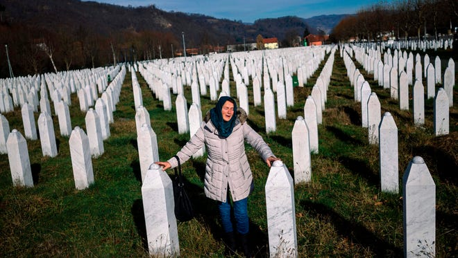 A woman mourns over a relative's grave at the SrebrenicaÐPotocari Memorial on Nov. 22, 2017. United Nations judges sentenced former Bosnian Serbian commander Ratko Mladic to life imprisonment after finding him guilty of genocide and war crimes in the brutal Balkans conflicts over two decades ago.