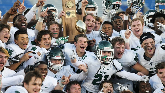 Trinity players carry the state championship trophy following their victory over St. Xavier during the Commonwealth Gridiron Bowl held at the UK football stadium on Sunday afternoon. Trinity won the state title 28-21. Dec. 3, 2017