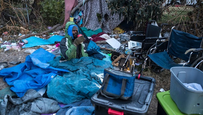 """Byron """"Roc"""" Peeler sat in his homeless camp between Jefferson Street and I-65 as policer arrived to remove him and others from the premises. Dec. 8, 2017."""