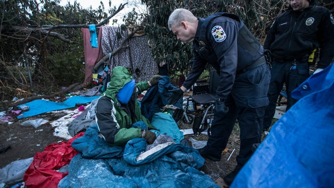"Metro Louisville Police Lt. Todd Felty talks with Byron ""Roc"" Peeler prior to removing him from a homeless camp between Jefferson Street and I-65. Dec. 8, 2017."