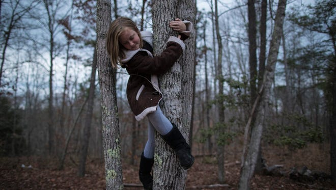 Andiria Tipton, 10, plays alone in the trees at dusk outside Appalachian Ministries. Nov. 30, 2017