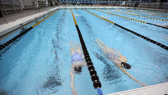 Ruby Martin, left, swims laps during practice at the Campus Recreation and Wellness Center on Monday, Dec. 11, 2017.