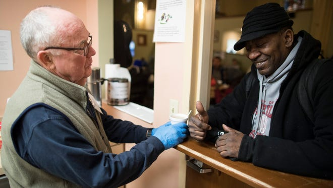 """Volunteer Dick Kaukas, left, hands a cup of coffee to Brian Phillips on Tuesday morning at St. John Center for the Homeless Men. """"This is a place to get out of the cold from 7 a.m. to 3 p.m. in the winter and from the heat in the summer,"""" Kaukas said. """"They can socialize and start on the process of getting a place of their own."""" Feb. 13, 2018"""