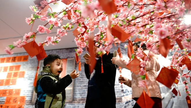 A boy plays under a prayer tree at an exhibition held in conjunction with Lunar New Year festivities in Shanghai, China on Feb. 10, 2018. Chinese worldwide are preparing to celebrate the Lunar New Year on Feb. 16 with family reunions, firecrackers, and traditional food as they welcome the Year of the Dog.