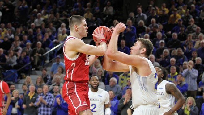 South Dakota State's Mike Daum (right) tries to defend against South Dakota's Matt Mooney during the second half of the Jackrabbits' 76-72 victory over the Coyotes Thursday night at Frost Arena.