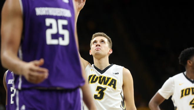 Iowa's Jordan Bohannon points to the sky after keeping Chris Street's consecutive free throw record intact during the Hawkeyes' game against Northwestern at Carver-Hawkeye Arena on Sunday, Feb. 25, 2018.
