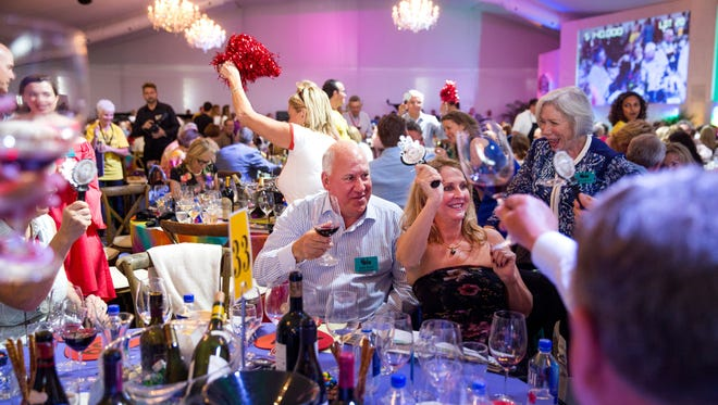 John Raitt and Diana Twyman celebrate after winning lot 20, Australia from the Bottom Up, during the Naples Winter Wine Festival Auction on Saturday, January 27, 2018 at the The Ritz-Carlton Golf Resort in Naples, Fla. Lot 20 sold for $140,000.