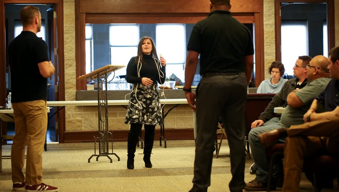 Jessica Peckover, Colin Fowler (left) and Juan Coleman demonstrate proper dialog when talking to people suffering from mental illness or substance abuse during crisis intervention training at Saint Patrick's Church on Wednesday, March 21, 2018.