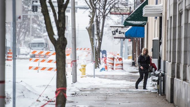 A woman walks past storefronts in the first block of North Eigth Street on a snowy morning Wednesday, March 21, 2018.