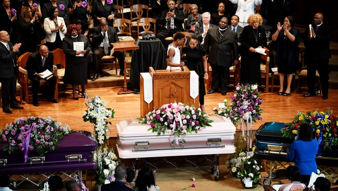 Tamika Foreman puts her hand over her face after singing a song at First Baptist Church of Asheville during the funeral of Erica Smith and her children, Harmony Smith and Keithan Whitmire April 27, 2018.