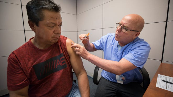 Jose Escamilla, left, receives a hepatitis A shot from Emilio Barrios Lazo, a medical assistant at the University of Louisville Travel Clinic. Escamilla is a food worker at a local restaurant. May 11, 2018