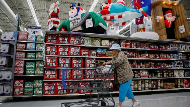 A woman pushes a shopping cart past Christmas decorations displayed for sale at a Wal-Mart Stores Inc. location ahead of Black Friday in Los Angeles, California, U.S., on Monday, November 24, 2014. Retailers are planning to open earlier on Thanksgiving day this year in a bid to draw shoppers. Wal-Mart Stores Inc. is making Black Friday, the shopping day after Thanksgiving, a week-long event this year.