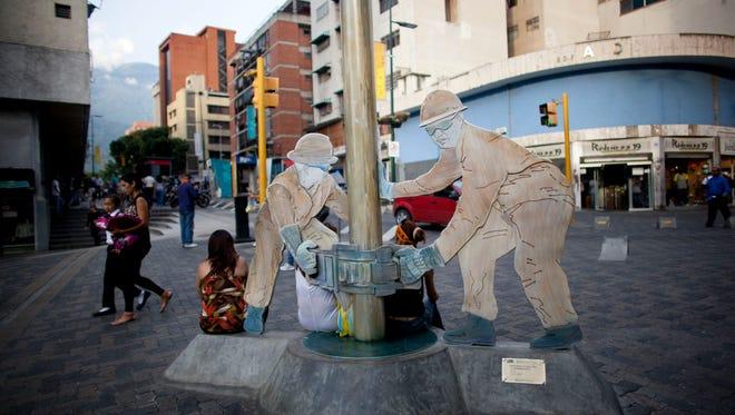 A sculpture of oil workers decorates a sidewalk in Caracas, Venezuela, on Oct. 23.