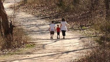 A family strolls along a trail inside Ritter Springs Park to enjoy the sunny weather.