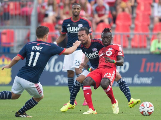 Toronto FC's Dominic Oduro, right, battles for the ball with New England Revolution's, from left to right, Kelyn Rowe, Darrius Barnes, and Daigo Kobayashi during the first half of a soccer game, Saturday, Aug. 30, 2014 at BMO Field in Toronto. (AP Photo/The Canadian Press, Darren Calabrese)