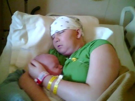 Ashley holds her newborn son as she battles stage 4 cancer.