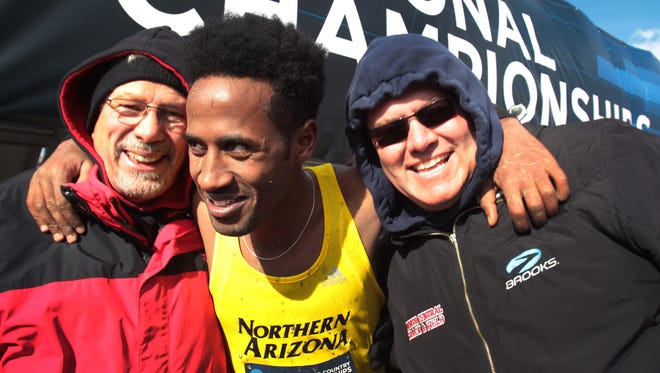 Futsum Zienasellassie, a Northern Arizona sophomore and 2012 graduate of North Central High School, Indianapolis, celebrates his fourth place finish in the NCAA Division 1 Cross Country championships with his former Panthers coaches, Rick Stover, left, and Byron Simpson after the men's championship race held in Terre Haute on Saturday, Nov. 23, 2013.