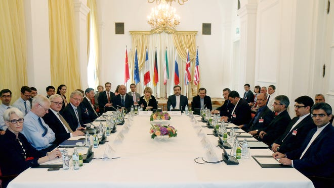 Delegates sit around a table before a meeting of the closed-door nuclear talks with Iran at a hotel in Vienna, Austria, Friday, June 12, 2015.