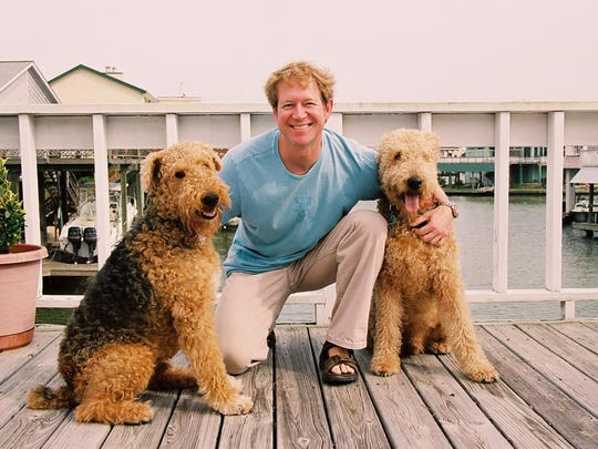 Father Bill Miller poses with his Airedale terriers.