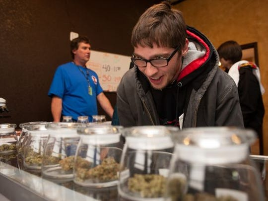 An Ohio man selects marijuana at a Colorado dispensary in 2014. In late February, Missouri officials  published draft rules pertaining to medical marijuana ID cards for patients and caregivers. The state is setting up its new medical marijuana system in 2019.