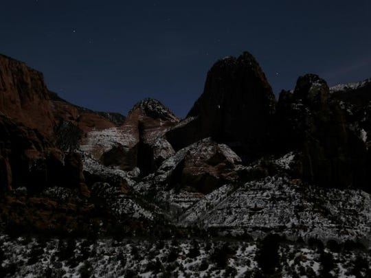 A near-full moon illuminates Kolob Canyon.
