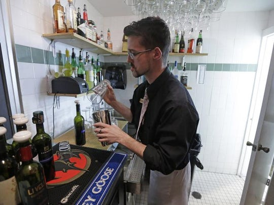 Vivace Restaurant Manager Dustin Humes fixes a drink