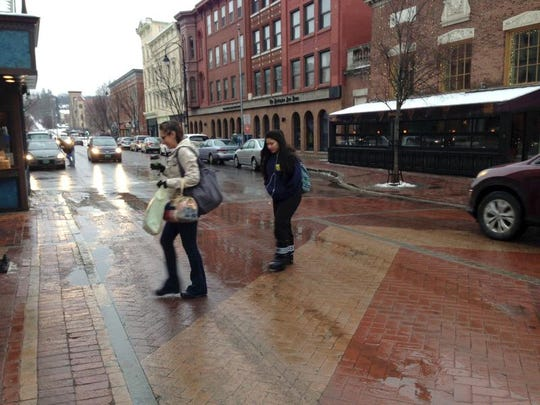 FILE: People walk gingerly across the intersection of Church and College streets in Burlington, as an icy film made for slippery conditions.