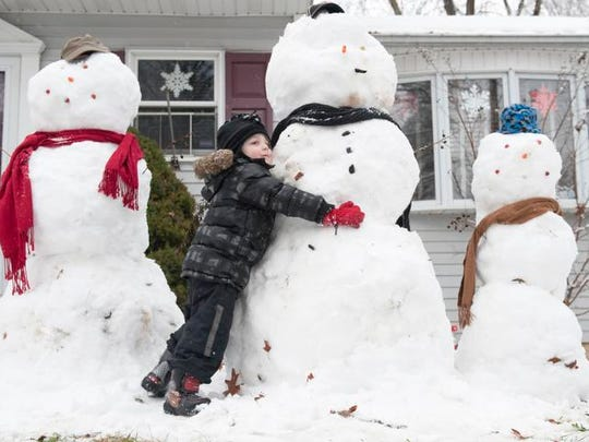 Logan Seitz, 3, of Oaklyn hugs one of three snowmen