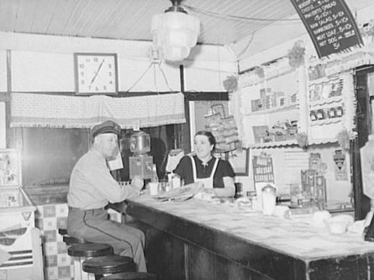A truck driver in a diner in Clinton, Ind., enjoys a meal before heading out on the road in February 1940.