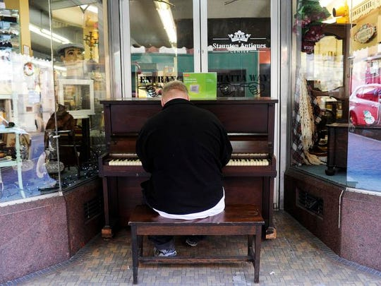 Michael Robertson plays the piano outside of Staunton Antiques Center on Tuesday, Dec. 31, 2013, in Staunton. Robertson never took piano lessons, but taught himself and learns songs by ear.