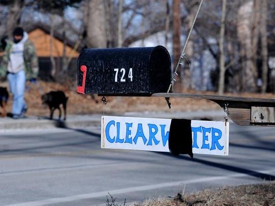 Leroy Williams walks with his dogs Wednesday past the Hudson River Sloop Clearwater office on Route 9D in Beacon. The Clearwater sign has a black banner in place to mourn its founder, Pete Seeger, who died Monday night.