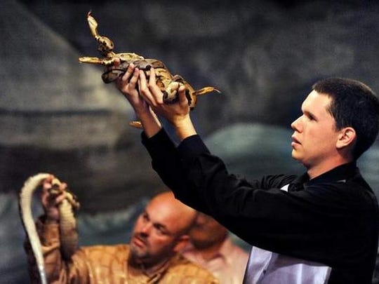 In this archive photo, Andrew Hamblin, pastor of Tabernacle Church of God in LaFollette, Tennessee, holds up four copperheads during church service while his mentor Jamie Coots, pastor of the Full Gospel Tabernacle in Jesus Name church of Middlesboro, Kentucky, holds a rattlesnake.