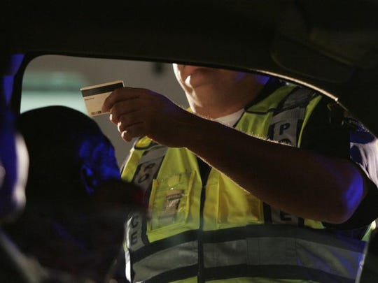 In this 2010 file photo, Palm Springs police Officer Art Enderle inspects a car at a DUI checkpoint.