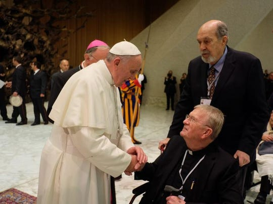 The Pope greets Bob Clausen's brother Bill, a priest who has attended 24 conferences at the Vatican in the past 28 years.