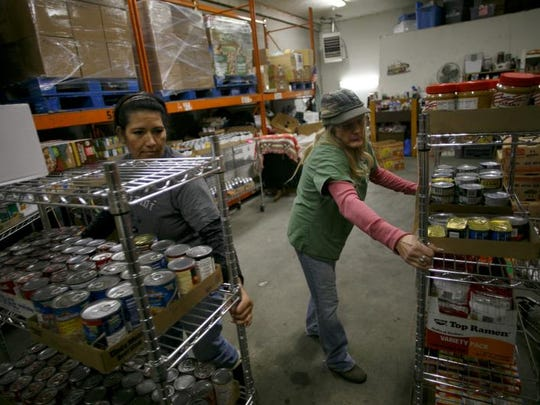 Roberta Cameron and Raynalda Stubbs, left, employees of the Hurricane branch of Dixie Care and Share, set up racks of canned goods and other foods Monday as they prepare the food bank to receive customers.