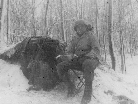 Gus Penzari poses in front of his shelter during the Winter of 1944-45.