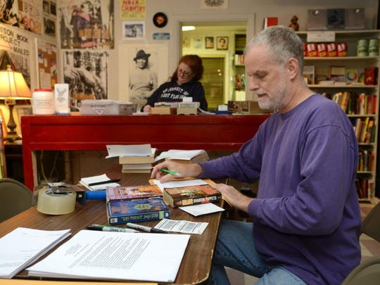Volunteer Johnny Ardis addresses and packs books recently at Open Books as part of the Prison Book Project. Each week, volunteers gather and pack donated books to ship to prisoners across the state.