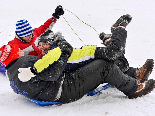 Charlie Primus (striped hat), 12, St. Cloud, his dad, Danny, and sister, Jennifer, 9, laugh as they careen down the sledding hill Dec. 26, 2013 at Calvary Hill Park in St. Cloud.