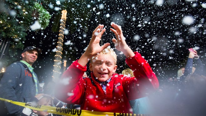 "Will Kramer, 9, looks up towards the ""snow"" during the annual Christmas on Third celebration in downtown Naples on Monday, Nov. 21, 2016. The event featured tree lighting, ice sculptures, music and fake snow."